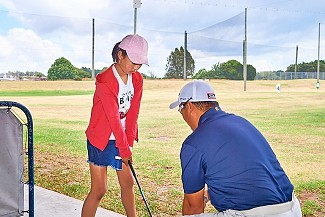 Sam coaching a junior golfer on the driving range