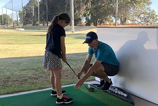 Scott coaching a young golfer